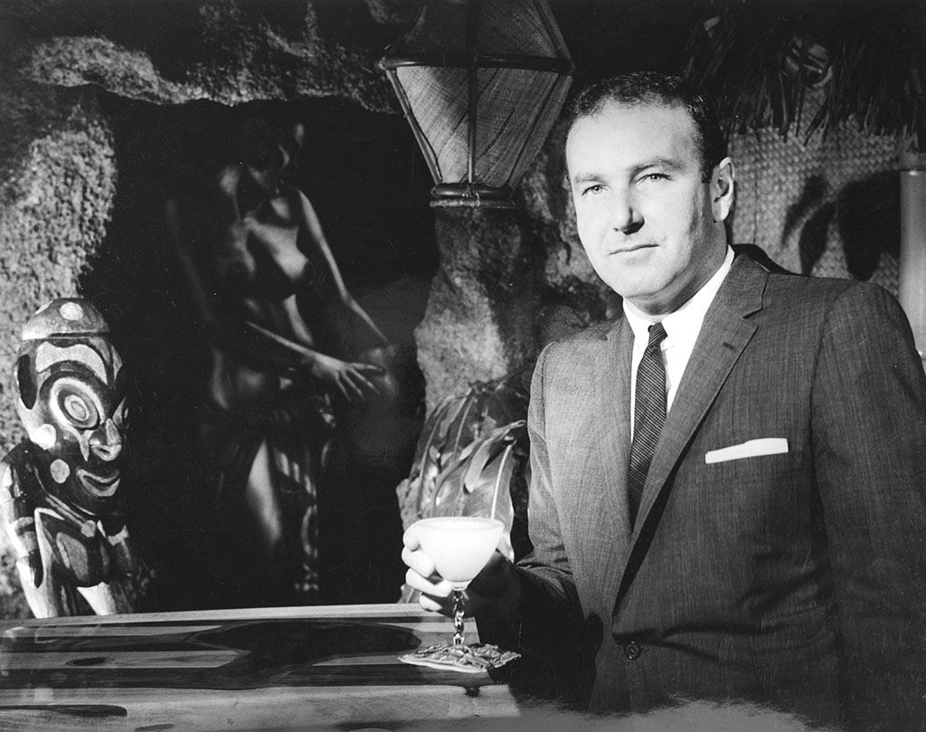 Vintage black and white photograph of Mr Thornton with glass next to Polynesian velvet painting.